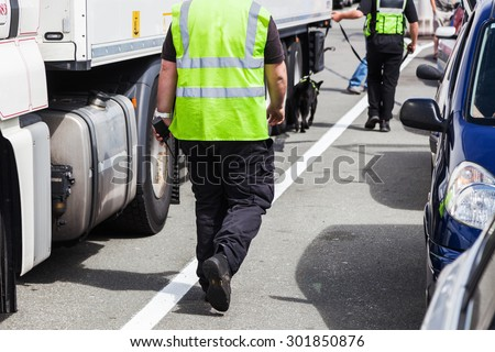 security personnel walking with a detection dog along lorries at a ferry port gate  - stock photo