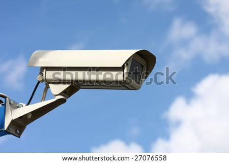 security video camera on background blue sky - stock photo