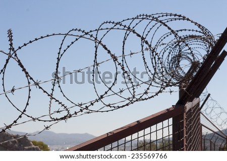 Security with a barbed wire fence photo. Protection concept design.  - stock photo