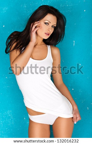 Seductive beautiful young woman in a casual white top and panties posing in front of a turquoise blue studio background