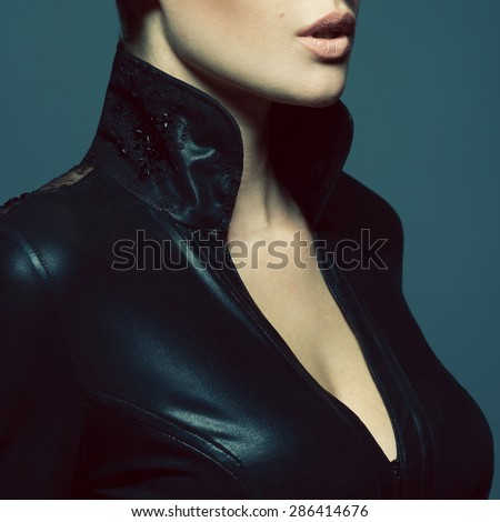 Seductive decollete concept. Profile portrait of beautiful young woman. Perfect natural make-up. Black leather dress with collar. Healthy skin. Close up. Studio shot - stock photo