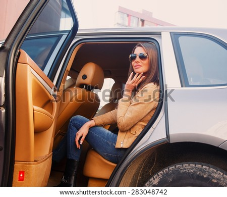 Seductive girl in sunglasses sitting in the car on back seats - stock photo