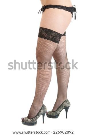 Seductive girl's legs wearing high heels, black stockings and black underwear - stock photo