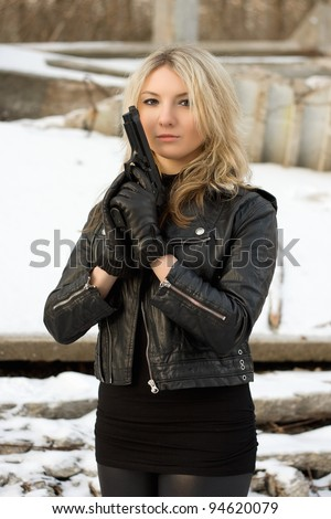 Seductive girl with a gun against the snow - stock photo