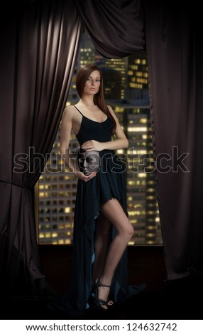 Seductive lady in evening dress with mask in her hands standing near the window, night city background