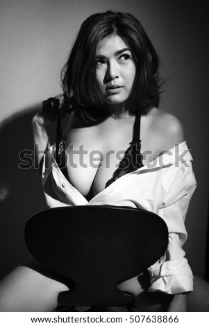 Seductive lady in short dress sits on the chair in black and white.