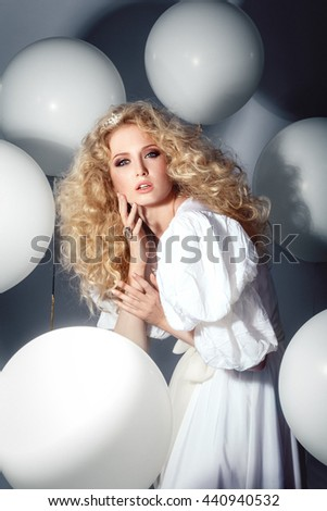 Seductive model in a white dress with balloons. Fashion.
