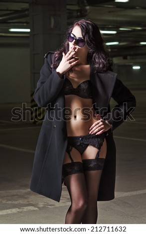 Seductive smoking young woman in black underwear and coat  - stock photo
