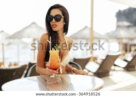Seductive woman drinking cocktail in summer