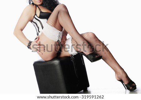 seductive woman in lingerie and stockings sitting on pouf on white background studio