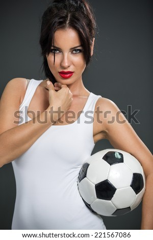 seductive woman posing with soccer ball, looking at camera - stock photo