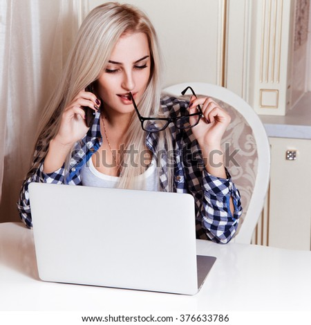 Seductive young blonde business woman talking phone and working on laptop. Technology mobility education concept - stock photo