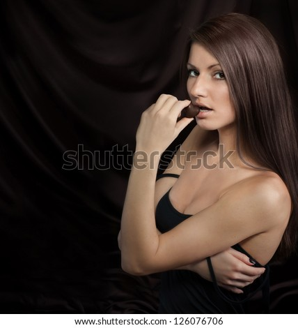 Seductive young woman biting chocolate candy, on dark background - stock photo