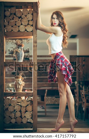 Seductive young woman posing in bar with wooden interior wearing western cowboy outfit - stock photo