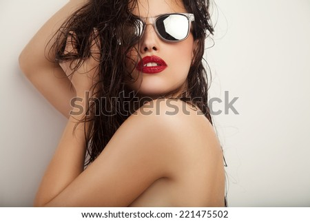 seductive young woman with red lips wearing modern sunglasses, studio white - stock photo
