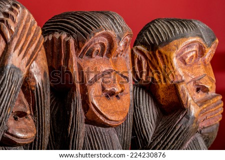 See hear speak no evil carved wooden monkeys on red background close up - stock photo