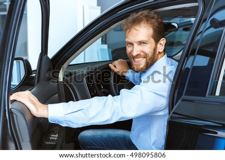 See you on the road! Handsome mature male customer sitting in a new car at the car dealership smiling to the camera through the open door