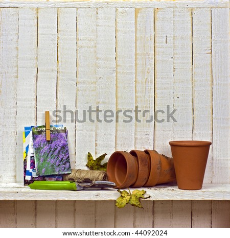 seeds, gardening tools and flowerpots on potting shed shelf; excellent copy space above main image - stock photo