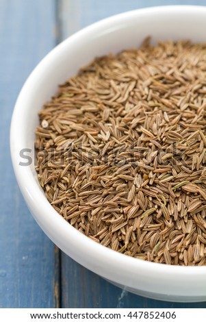seeds of carum in white bowl on blue background