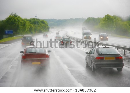Seeing as there's heavy shower on a highway and road condition looks quite dangerous. - stock photo