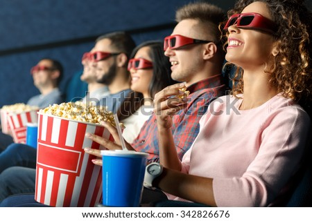 Seeing it in 3d. Friends sitting and eating popcorn together while watching movies at the cinema - stock photo