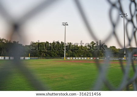 Seeing through chain link for a light post at a baseball field  - stock photo