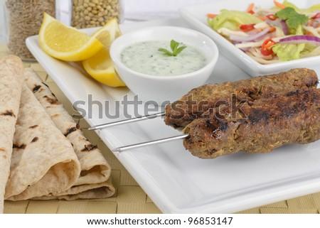 Seekh Kebab - Minced meat kebabs on metal skewers served with mint raita, crunchy salad, lemon wedges and chapatis. - stock photo
