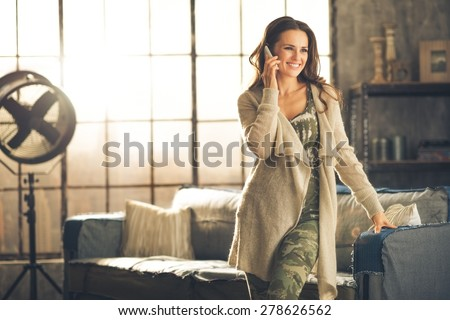 Seen from the front, a brunette woman in comfortable clothing is standing in a loft living room, leaning against the sofa, talking on her phone and smiling. Urban chic loft decoration details. - stock photo