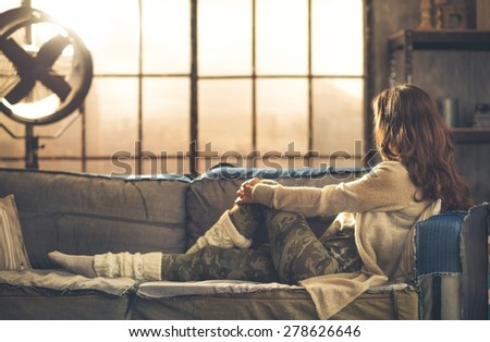 Seen from the side, face hidden by hair, a woman is sitting on a sofa looking out a loft window. Sun shines off the industrial fan. Industrial chic ambiance and urban feel. - stock photo