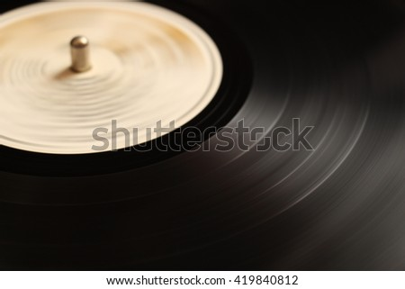 Segment of vinyl record with label spinning on turntable. Vinyl grooves background. - stock photo