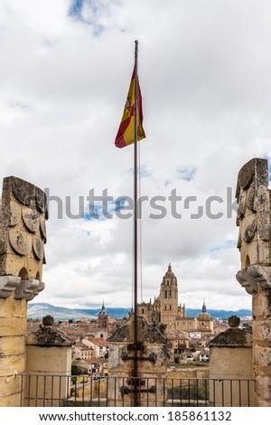 SEGOVIA, SPAIN - APR 5, 2014: Spanish flag in Alcazar of Segovia (Segovia Castle), a stone fortification, Segovia, Spain. It's one of the inspirations for Walt Disney's Cinderella Castle. - stock photo