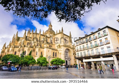 SEGOVIA, SPAIN - NOVEMBER 13, 2014: Pedestrians walk below Segovia Cathedral at Plaza Mayor. The cathedral dates from the mid 16th century. - stock photo