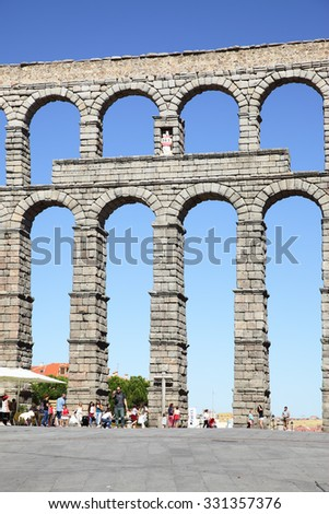 SEGOVIA, SPAIN - September 20, 2015: Ancient roman aqueduct in Segovia and tourists walking around, aqueduct was built about 2000 years ago - stock photo