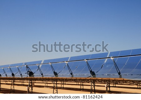 SEGS solar thermal energy electricity plant with parabolic mirror solar collectors concentrating the sunlight and blue sky copy space - stock photo