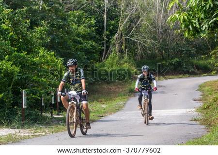 Selangor, Malaysia - 28 January 2016 : Mountain bikers ride on through a rubber estate in Semenyih on January 28. - stock photo