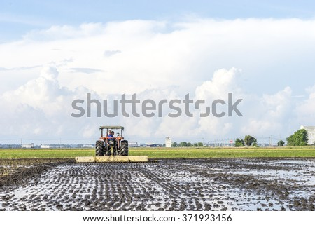 SELANGOR, MALAYSIA - JANUARY 31, 2016: Worker uses a machine to tilling the soil for planting rice on paddy field in Sekinchan, Malaysia. Sekinchan is one of the major rice supplier in Malaysia.