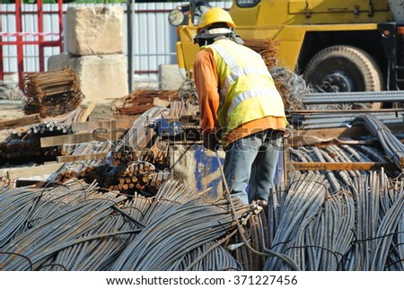 SELANGOR, MALAYSIA MARCH 17, 2015: Construction workers working at steel bar bending yard in construction site in Selangor, Malaysia.