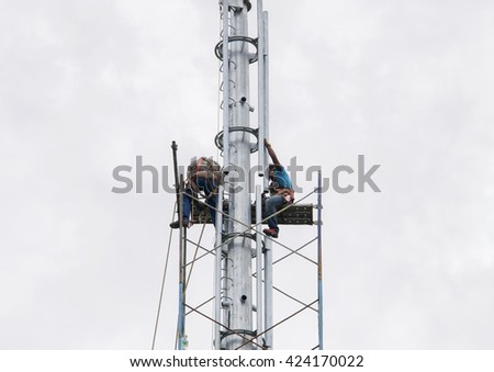 SELANGOR, MALAYSIA - MAY 21, 2016: Riggers are working at top of the monopole for installing scaffolding before radio frequency antenna and microwave dish installation.