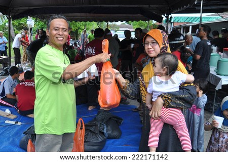 SELANGOR, MALAYSIA-Oct 5: An unidentified Muslim distributes meat to the poor during Eid Al-Adha Al Mubarak, the Feast of Sacrifice on October 5, 2014 in SELANGOR , Malaysia - stock photo