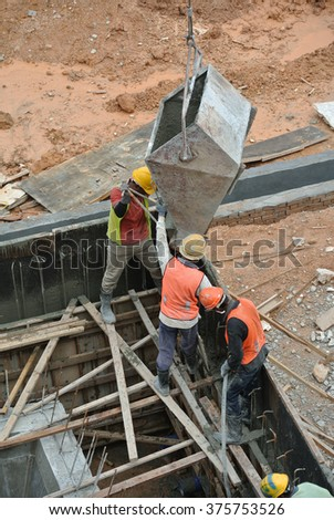 SELANGOR, MALAYSIA - OCTOBER, 2014: Group of construction workers casting reinforcement wall on October 09, 2014 at Sepang, Selangor, Malaysia. The concrete was lifted using basket from mobile crane.