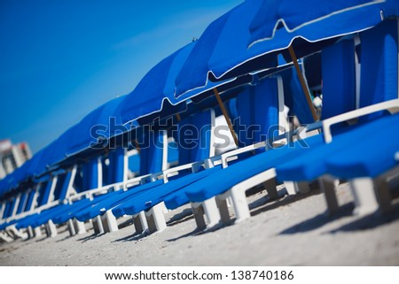 Select focus of Row of Blue Lounge chairs and umbrella on beach. - stock photo