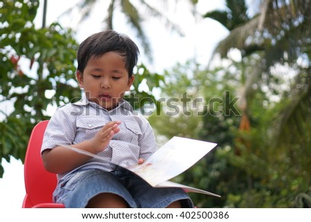 Selected focus cute boy in summer park sitting on chair and reading book (Blur background)