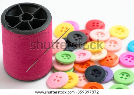 Selected focus on needle with thread. defocus buttons, sew instrument isolated on white background - stock photo