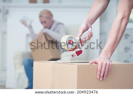 Selected focus on the box which is pasted up by some man. Attractive blonde sitting on the cosy sofa on background - stock photo