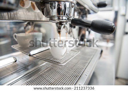 Selected focus on the coffee pouring into the white cups. Coffee machine on background - stock photo