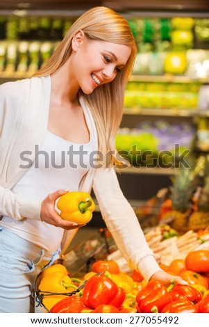 Selecting freshness and quality. Beautiful young women holding pepper and smiling while standing in a food store - stock photo