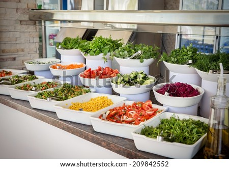 Selection of assorted healthy fresh salads displayed in individual dishes at a restaurant or catered event, healthy food - stock photo