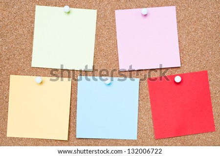 Selection of blank adhesive notes attached to a cork board - stock photo