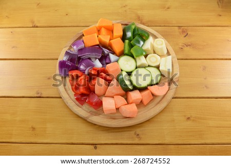 Selection of chopped vegetables on a wooden chopping board - butternut squash, green pepper, parsnip, courgette, sweet potato, red pepper and red onion - stock photo