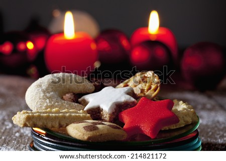 Selection of christmas cookies on plate on wooden floor burning candles in background - stock photo
